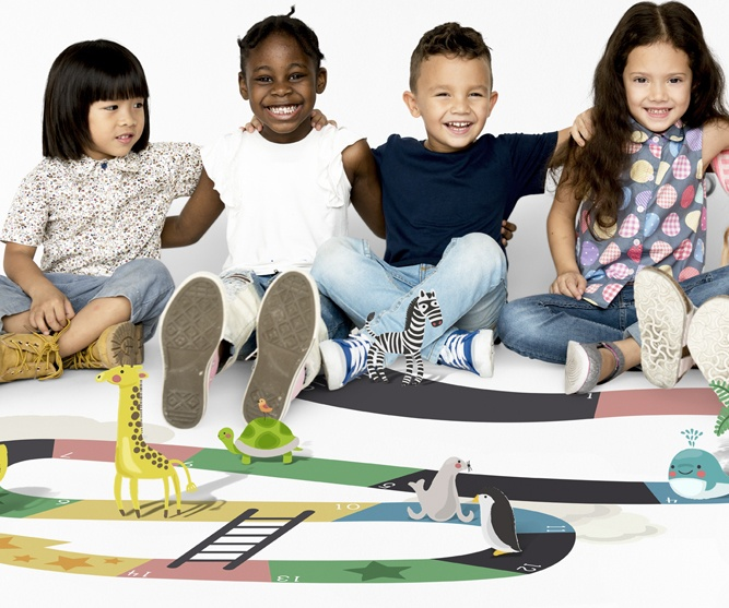 group of kids sitting on giant game board