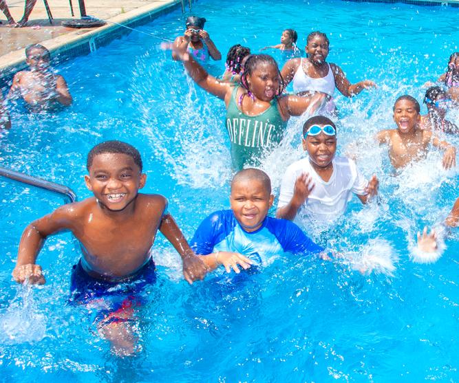 a group of kids splashing having fun in the pool
